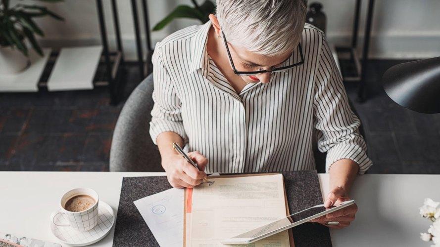 Mujer mayor sentada en el escritorio mirando la tableta mientras toma notas sobre el futuro de la experiencia del empleado