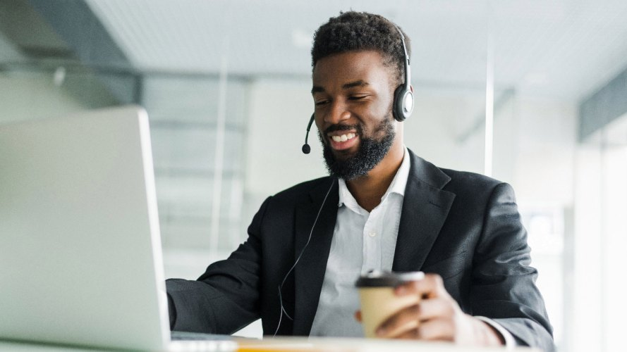 Agente de servicio al cliente con auriculares y café en una mano mirando la pantalla de su computadora portátil: automatice los procesos comerciales: TI, CIO