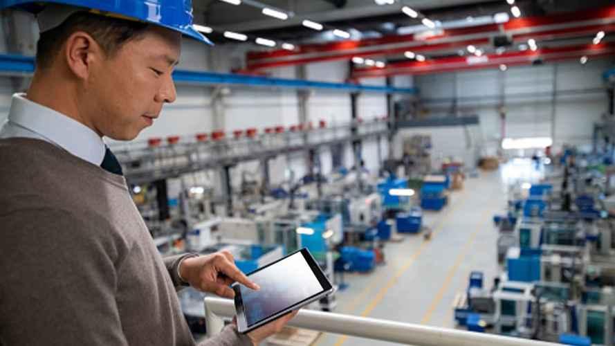 Trabajador con su tableta en la planta de fabricación