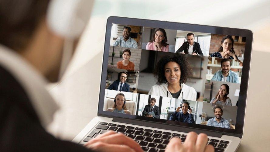 Hombre mirando una pantalla llena de colegas en una conferencia telefónica: investigación de pulso de experiencia de empleado