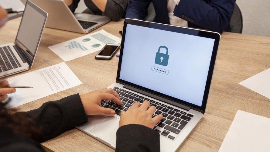 computadoras portátiles en una mesa con las manos, la pantalla de la computadora portátil tiene una imagen de un candado que indica cómo evitar ataques de ciberseguridad