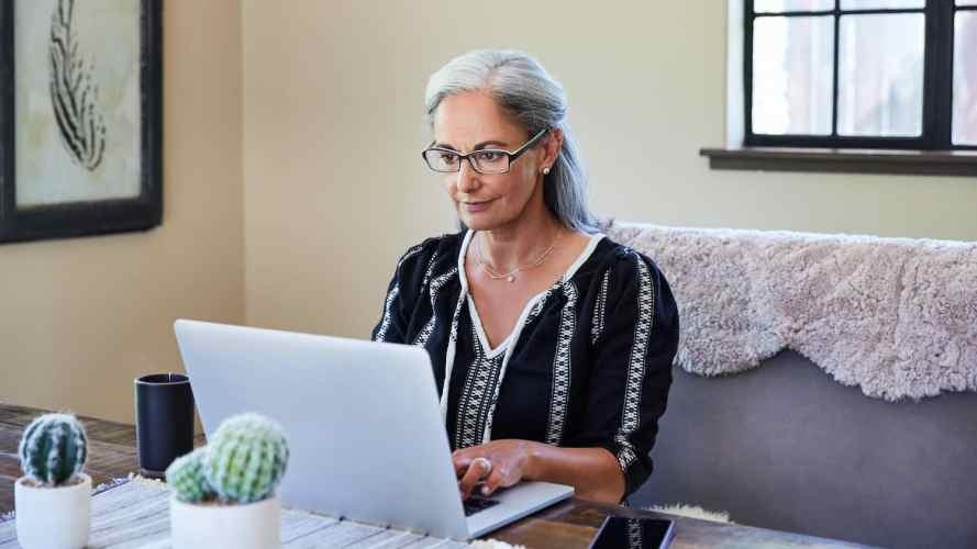 Mujer madura trabaja en su computadora portátil